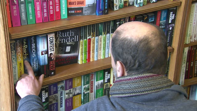 Interior shots customer and shop assistant browsing books on shelves in book shop on January 02 2014 in Ely England