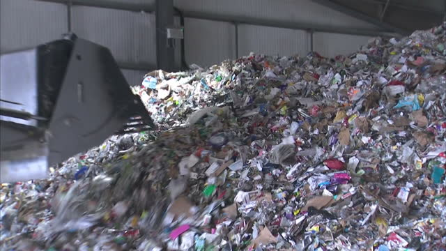 interior shots digger moving big pile of cardboard due to be recycled & shots of cans squashed into cubes in recycling centre on december 28, 2016 in... - 廃棄物処理点の映像素材/bロール