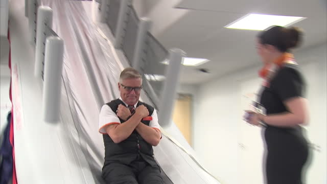 interior shots easyjet trainee cabin crew taking part in training exercise using emergency plane slide at easyjet's new training academy at gatwick... - crew stock videos & royalty-free footage