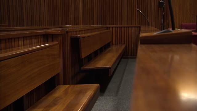 interior shots empty court room w/ bench microphone metal detector by door - court room点の映像素材/bロール