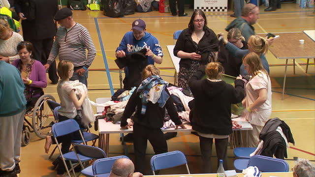 vidéos et rushes de interior shots flood evacuation centre in sports hall with people sat at tables eating food. exterior shots makeshift camp beds northampton flood... - northampton