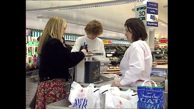 interior shots food items being swiped through scanner shoppers bagging up food items and paying for shopping at checkout tills in tesco supermarket... - tesco点の映像素材/bロール