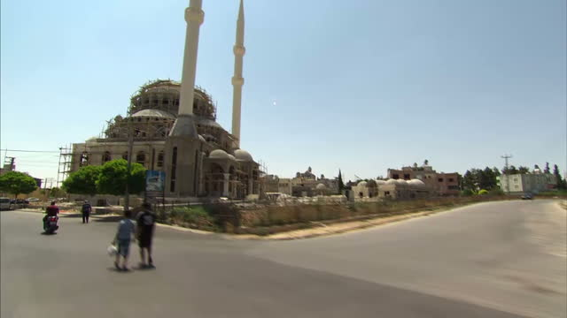 vidéos et rushes de interior shots from a vehicle travelling through the streets of kilis travelling past residential buildings and a mosque surrounded by scaffolding>>... - entourer