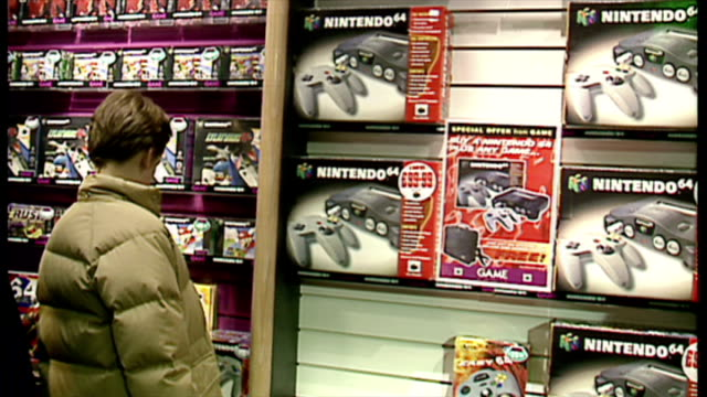 interior shots gamers browsing nintendo 64 games and consoles on shelves in game video game store on december 22 1997 in london england - raw footage stock videos & royalty-free footage