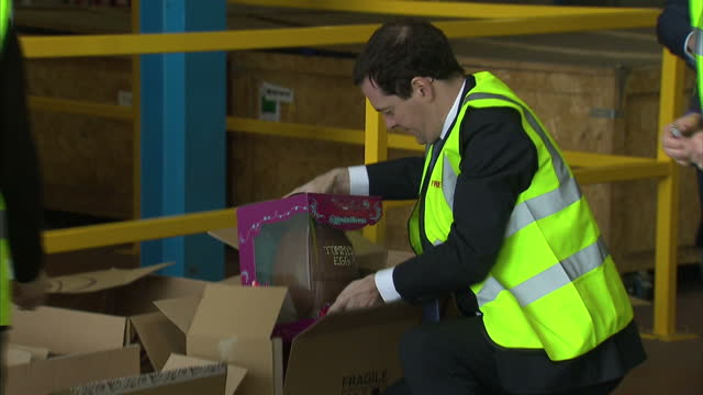 interior shots george osborne chancellor of the exchequer being show around freight first warehouse and helps to pack easter eggs into freight boxes... - チャンセラー点の映像素材/bロール