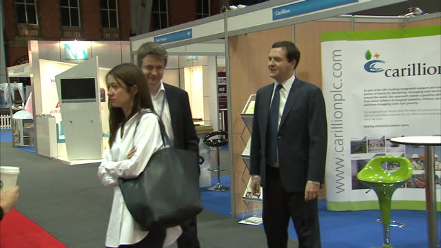 Interior shots George Osborne Chancellor of the Exchequer walking past stands including Carillion Royal Mail at the Conservative Party Conference...