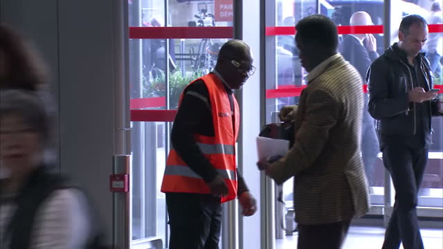 Interior shots increased security personnel at Charles De Gaulle Airport in Paris including police officers with police dogs near entrance and armed...