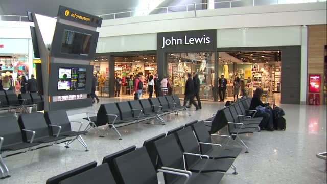 vidéos et rushes de interior shots john lewis store in heathrow terminal 2 with passengers browsing items in shop and pulling suitcases around. on june 04, 2014 in... - format raw