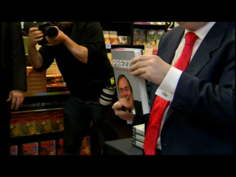 vidéos et rushes de interior shots john prescott poses for pictures holding autobiography 'prezza pulling no punches' interior shots prescott signing copies of his... - biographie