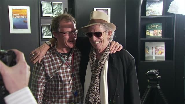 """interior shots keith richard poses with members of the press for pictures & signs a copy of his autobiography """"life"""" keith richards at book signing... - biographie stock-videos und b-roll-filmmaterial"""
