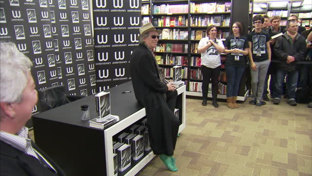 "interior shots keith richards poses for the press with a copy of his autobiography ""life"" ahead of his book signing keith richards poses at book... - autobiography stock videos & royalty-free footage"