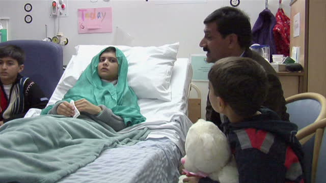 vídeos y material grabado en eventos de stock de interior shots malala yousufzai lying in hospital bed surrounded by her family malala yousufzai with family in hospital on october 26 2012 in... - niña en edad escolar