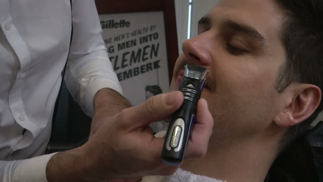 interior shots man sat in barber shop having his movember moustache shaved off it's razors at the ready for thousands of men across the uk today a... - movember stock videos & royalty-free footage