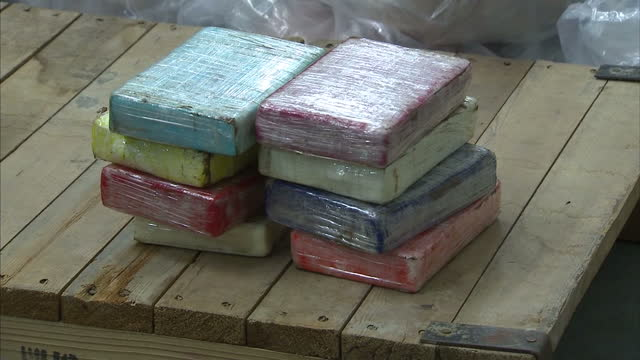 interior shots massive pile of cocaine packages stacked in bundles of plastic bags with police officers sorting through them interior shots packages... - cocaine stock videos and b-roll footage