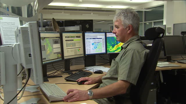 interior shots met weather office workers analysing storm impact. working at desks and following storm projections on monitors. huge storm forecast... - exeter england stock videos & royalty-free footage