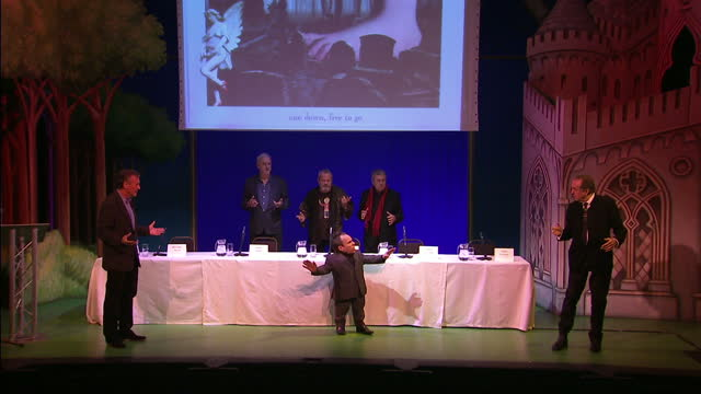 interior shots monty python members on stage all talking at once & warwick davis wlks & tells them to be quiet monty python stars announce reunion... - monty python video stock e b–roll