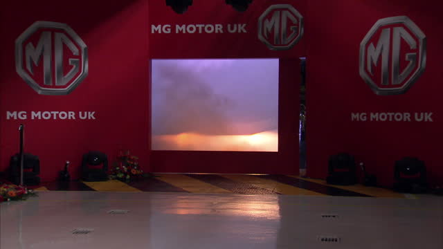 stockvideo's en b-roll-footage met interior shots new mg6 car is driven onto stage at the longbridge plant to applause with female factory worker getting out of the car &b posing for... - plant stage