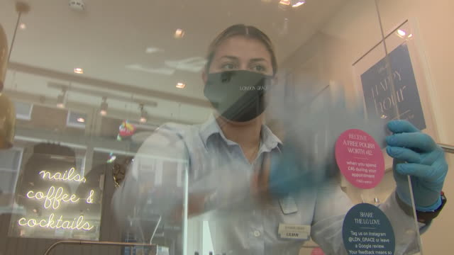 interior shots of a beautician donning protective latex gloves and using spray cleaner to clean a perspex protective screen, and manicuring tools in... - ラテックス点の映像素材/bロール