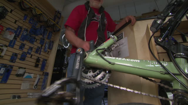 interior shots of a bike shop employee slowly rotating the chain and pedals of a vintage bicycle on 10 may 2019 in washington dc united states - pedal stock videos & royalty-free footage
