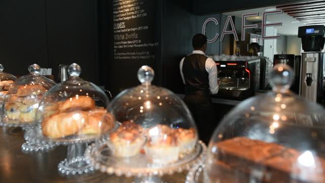 vídeos de stock, filmes e b-roll de interior shots of a cafe in the lobby of the virgin hotel in chicago illinois shots rak focus from a row of pastries under glass to an employee... - característica de construção