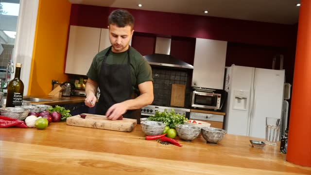 interior shots of a chef chopping red onions preparing food in a kitchen on 14 november 2017 in london united kingdom - chilli con carne video stock e b–roll
