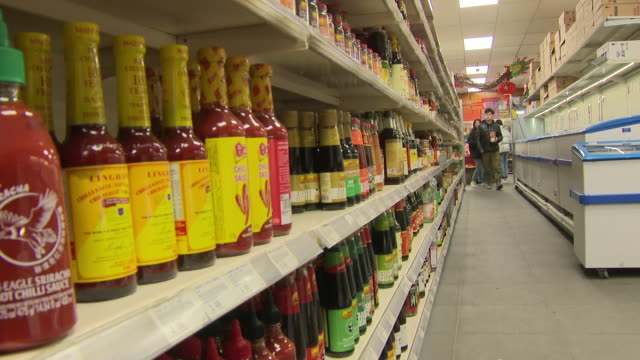 vídeos de stock e filmes b-roll de interior shots of a chinese supermarket including shots of people waiting in a queue cashier taking payment for items people looking though in the... - caixa de balcão