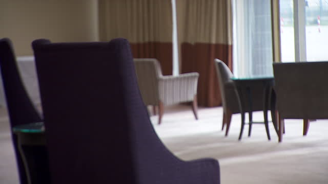 interior shots of a covid-19 quarantine hotel lounge room with chairs positioned to adhere to social distancing guidlines and view of heathrow... - solitude stock videos & royalty-free footage