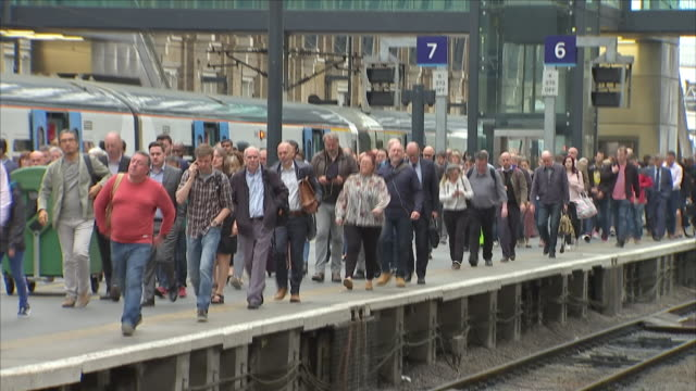 Interior shots of a crowd of passengers walking along a train platform and going towards the exit at King's Cross railway station on 6th June 2018 in...