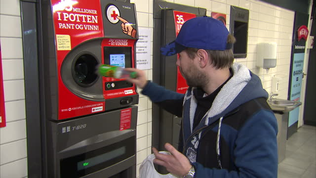 Interior shots of a deposit return point in a Meny supermarket including shots of a man putting bottles and cans into one of the machines and taking...
