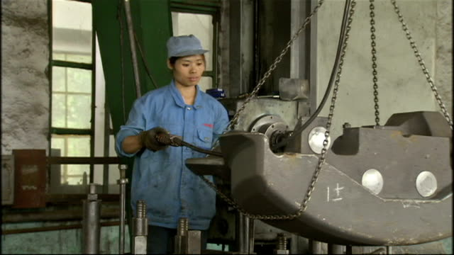 vídeos de stock e filmes b-roll de interior shots of a female factory worker in a steelworking plant moving a large heavy steel object around the factory floor by a remotely operated... - moving activity