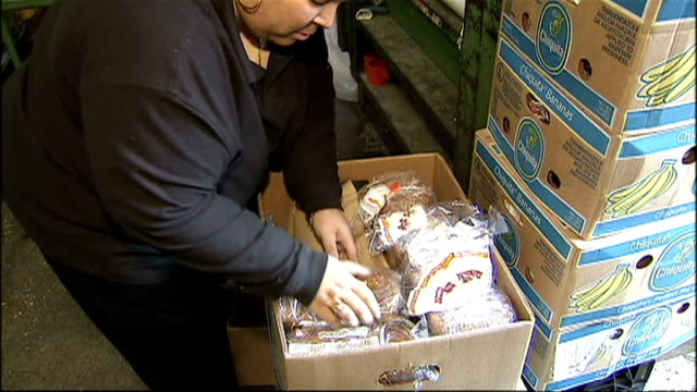 interior shots of a giant supermarket employee in the back of house warehouse area packing shop soiled goods into boxes for distribution to food... - warehouse点の映像素材/bロール