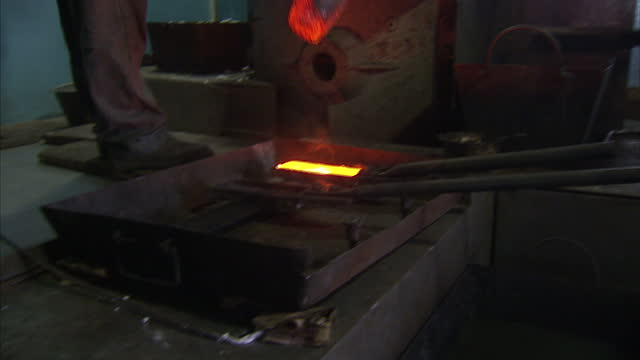 interior shots of a gold smelter at work in protective clothing taking pot of molten gold from furnace and pouring it into a gold ingot cast on may... - molten stock videos & royalty-free footage