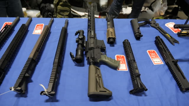 interior shots of a protrump political stand with activists at a st louis gun show and people browsing various stands of automatic weapons and... - gun stock videos & royalty-free footage