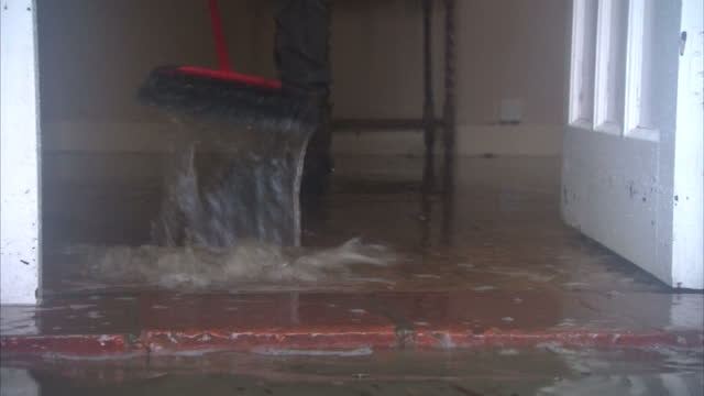 interior shots of a resident sweeping flood water out of his home winter floods have affected various parts of the uk winter floods damage homes... - 2013 stock videos & royalty-free footage