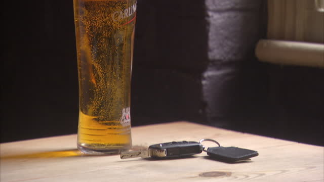 interior shots of a tall pint of lager on a table, panning to show a car key fob lying next to the glass.>> on august 10, 2014 in isleworth, england. - lager stock videos & royalty-free footage