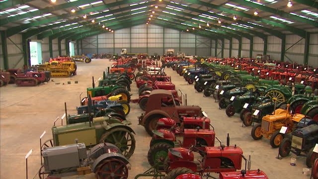 interior shots of a vast number of vintage tractors parked in lines each with a board outlining its history on september 15 2015 in thetford england - collection stock videos & royalty-free footage