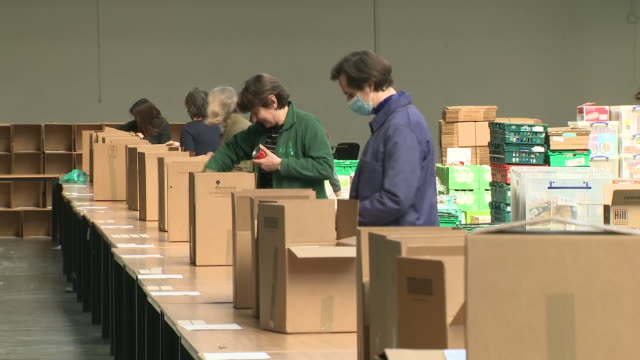 interior shots of a warehouse being used as a food bank in white city with volunteers packing food products from pallets into boxes for needy people... - packing stock videos & royalty-free footage