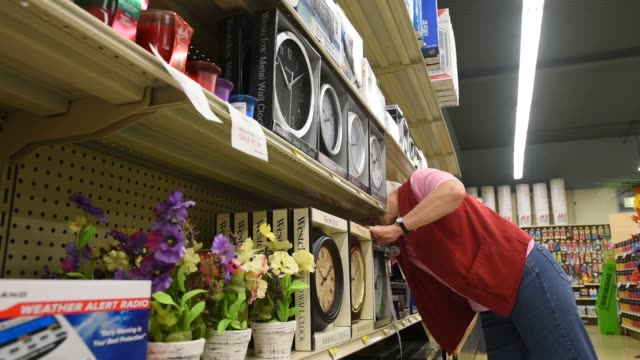 Interior shots of an Ace Hardware employee dusting the shelves inside the hardware store Interior shots of employees assisting customers inside a...