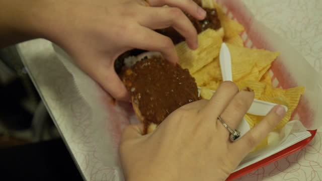 interior shots of an anonymous diner eating a chilli dog and chips in ben's chilli bowl fast food restaurant on december 13 2014 in washington dc - overweight dog stock videos & royalty-free footage