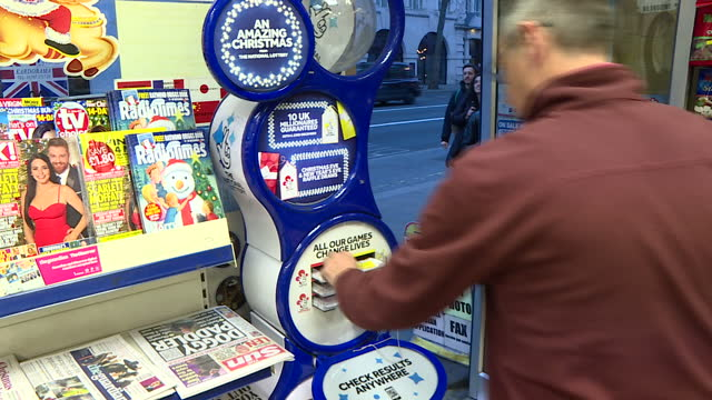 interior shots of an anonymous man filling in a national lottery ticket in a newsagents shop, with camelot branding on the lottery stand adverrtising... - 宝くじ点の映像素材/bロール