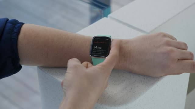 vidéos et rushes de interior shots of an anonymous person wearing an apple watch fitness tracker and using its on-screen functions on 13 march 2019 in cupertino, united... - montre intelligente