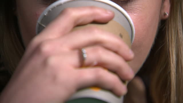 interior shots of an anonymous woman sipping coffee from a takeaway cup and making slurping noises to demonstrate the condition of misophona where... - coffee drink stock videos & royalty-free footage