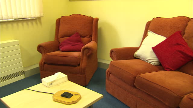 vídeos de stock e filmes b-roll de interior shots of an empty consultation room in a swindon rape crisis centre with posters warning of the symptoms of domestic abuse seating and cctv... - domestic room