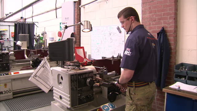 stockvideo's en b-roll-footage met interior shots of an engineer in a workshop working on andy green's prospective 1000mph record breaking bloodhound car manufacturing a part using a... - recordbrekend