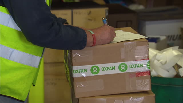 Interior shots of an OXFAM worker preparing packages of humanitarian aid for distribution to the Philippines at an OXFAM warehouse as part of Typhoon...