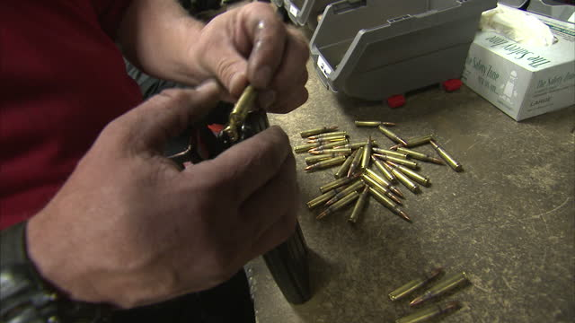 interior shots of anon men handling bullets ammunition and loading them by hand into machine gun clips gun clips being loaded with bullets at machine... - ammunition bildbanksvideor och videomaterial från bakom kulisserna