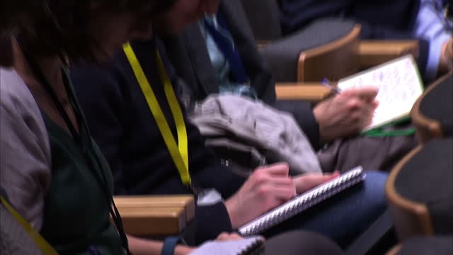 Interior shots of anonymous people taking notes in a conference and scrolling through news feeds on smartphones