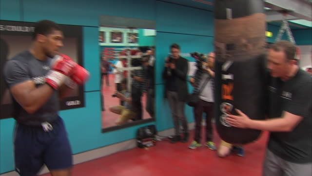 vídeos de stock e filmes b-roll de interior shots of anthony joshua resting then gets up and starts hitting punching bag with trainer rob mccracken on september 5th 2018 in sheffield,... - instrutor