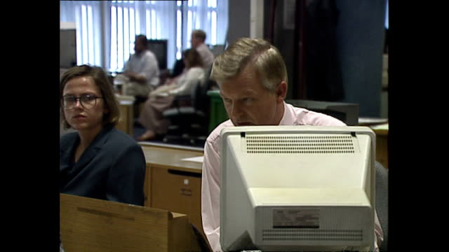 interior shots of bbc journalists working at computers and speaking on phones in the newsroom at television centre on may 20 1992 in london england - bbc video stock e b–roll