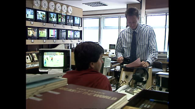 interior shots of bbc journalists working at computers and speaking on phones in the newsroom at television centre on may 20, 1992 in london, england. - bbc bildbanksvideor och videomaterial från bakom kulisserna